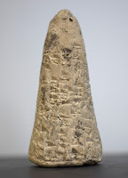 A photograph of a cone-shaped piece of clay, marked with cuneiform.