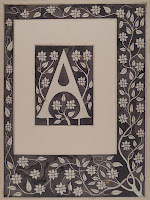 "A printed capital ""A,"" backed and framed a a flowering branch grows around the border of the print."