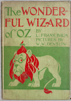 "A photograph of a cloth book cover. The text reads ""The Wonderful Wizard of Oz By Frank L. Baum Pictures by W. W. Denslow"" in red and green. The backdrop is beige and shows a bespectacled cartoon lion with a small bow in its mane, also in red and green."