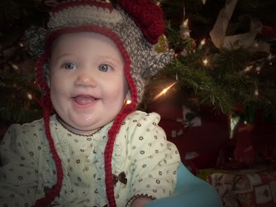 baby wearing a sock monkey hat in from of the Christmas tree