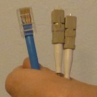 copper RJ45 and fibers held in a hand
