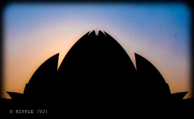 Sunset View @ Lotus Temple, Nehru Place, Delhi: The Baha'i House of Worship in Delhi which is popularly known as the Lotus Temple due to its flower like shape, is a Bahai House of Worship and also a prominent attraction in Delhi. It was completed in 1986 and serves as the Mother Temple of the Indian subcontinent. It has won numerous architectural awards and been featured in hundreds of newspaper and magazine articles.: Posted by Ripple (VJ) on PHOTO JOURNEY @ www.travellingcamera.com : ripple, Vijay Kumar Sharma, ripple4photography, Frozen Moments, photographs, Photography, ripple (VJ), VJ, Ripple (VJ) Photography, Capture Present for Future, Freeze Present for Future, ripple (VJ) Photographs , VJ Photographs, Ripple (VJ) Photography : Sun behind Lotus Temple throwing nice colors in the sky... I love this combo of Orange and Blue.. Although its hard to find these colors in Delhi but I was fortunate enough to catch it in my Camera :-)Lotus Temple is one of the most beautiful temples of India. Lotus Temple stands seventh in the international chain of Bahai House of Worship. Lotus Bahai Temple is considered as the Mother Temple of the Indian Continent. The splendid architecture of the temple has been accredited with several architectural awards.