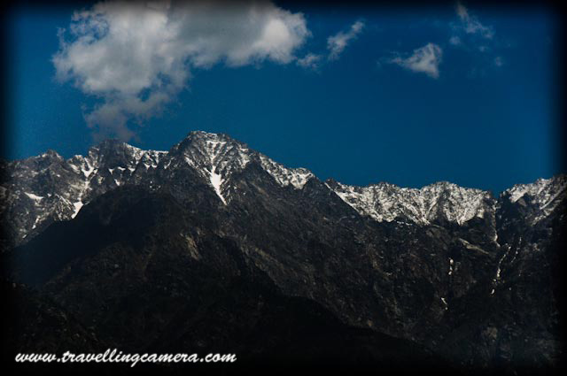 Glimpses of Palampur Town with Travelling Camera: Posted by VJ Sharma @ www.travellingcamera.com : Palampur, a dream place to live... Really, I have been to Palampur many times and more I visit this place, more I fell in love with this place... Town with wonderful views of snow covered Dhauladhar Mountains, Naturally rich has most of the modern facilities available...Here is a view from Tea Gardens near Neugal Cafe...Just entered into Palampur Town: From this Photograph you can make an idea that mountains around Palapur are clearly visible from most of the areas in this town... Weather in this town is amazing... Its not as crowded as Shimla and is comparatively rich in terms of basic facilities like Water, Light etc..A Photograph shot from moving car in the middle of Palampur Market... You can also see snow covered hills from here also ;-) .. Palampur Market is lovely place to spend your evenings..Most of the telecommunication service providers are there in Palampur and its not only the case for telecom services, but other types are services are also available with broad range of varieties. Palampur is very well connected through Bus, Train and there is also an Airport in Kangra....More clear view of Dhauladar Mountains from Neugal Khad....Palampur was a part of the local Sikh Kingdom before it came under the British raj. It was one of the leading hill states and was once a part of the Jalandhar kingdom. There are countless water streams, tea gardens and rice paddies. The town of Palampur came into being when Dr. Jameson who was Superintendent of Botanical Gardens and introduced the tea bush from Almora in 1850. The bush thrived and so did the town which became a focus of the European tea estate owners. Since then the Kangra tea of Palampur has been known internationally.