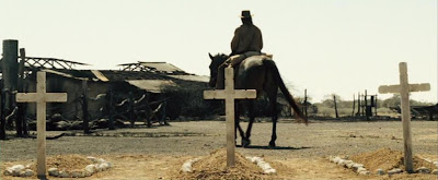 Charlie rides past three graves and a ruined house.