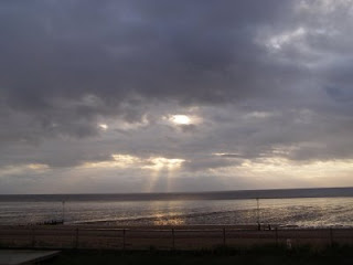 The sun, behind clouds, over the sea