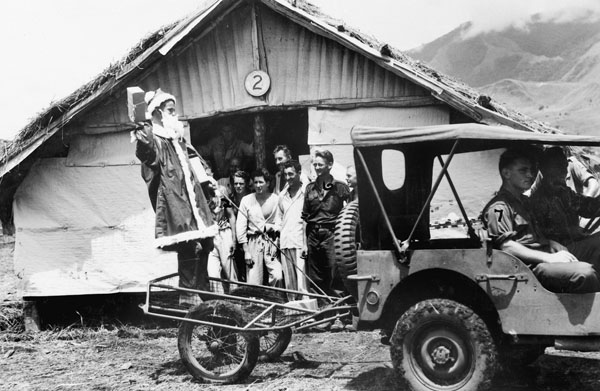Ramu Valley, New Guinea, 1943. NX103434 Captain F. D. Smith, dressed as Father Christmas, arriving at one of the wards of the main dressing station, 2/6th Australian Field Ambulance, in a jungle cart (Thompson Stretcher), drawn by a jeep, to distribute Christmas presents to the patients. Identified personnel are: SX28258 Private E. J. Cummings; TX5952 Private R. G. Viney, and Corporal R. Roessler.