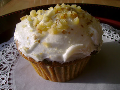 pumpkin spice cupcake topped with vanilla frosting and chopped walnuts