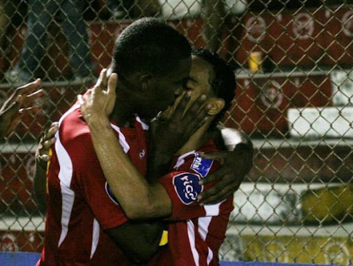 Brayan Beckeles and Orlin Peralta kissing during a goal celebration