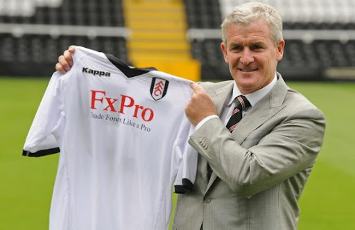 New Fulham manager Mark Hughes poses for photographers with a team shirt