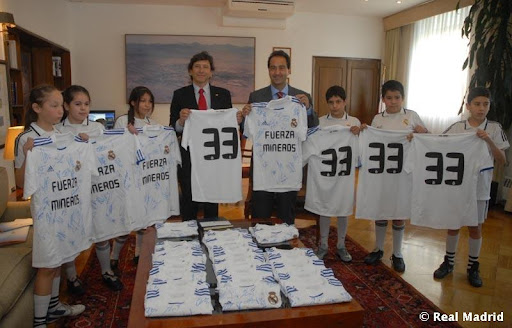 Santiago Mayor, Pablo Zalaquett, and Minister of Mining, Laurence Golborne, hold Real Madrid jerseys with children of the Friends of Real Madrid Foundation