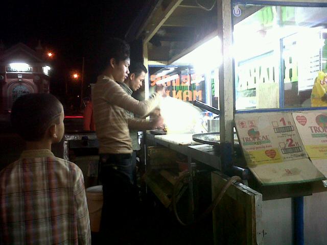 pedagang martabak sedang melayani pembeli