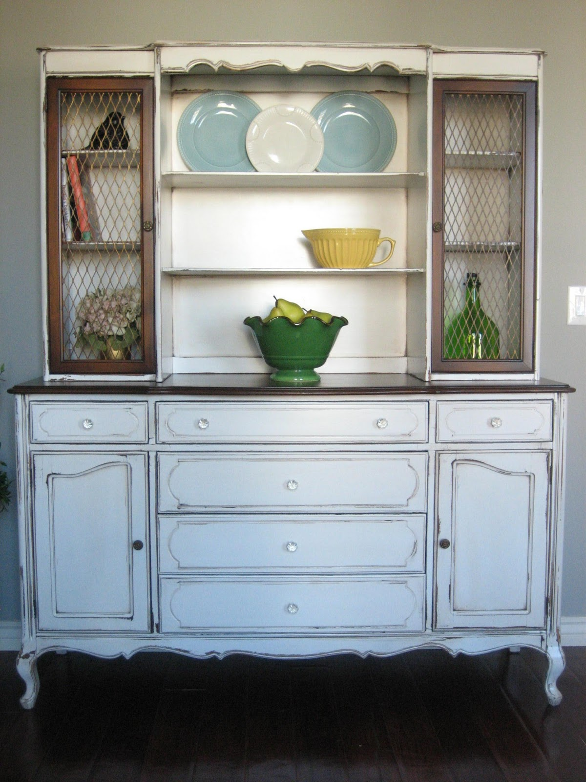 Creamy White Hutch With A Chippy Distressed Finish Dark Brown Stained Buffet Top And Upper Cabinets Have Brass Chicken Wire Hardware