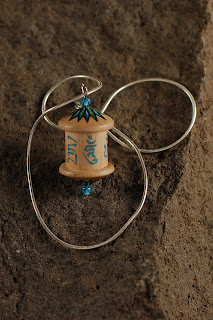 A WOODEN PRAYER WHEEL PENDANT