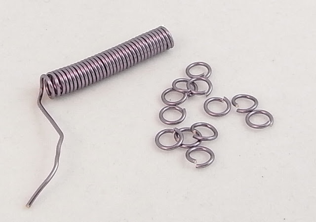 Some of the jump rings cut from the coil and the remaining coil ready for cutting into jump rings.