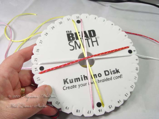 Set up your Kumihimo disk with the cords placed at the top and bottom, and right and left hand sides.