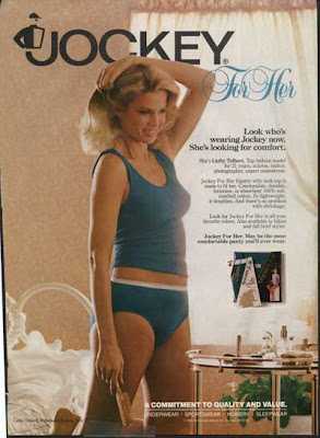 Woman in blue jockey underwear, standing in her bedroom