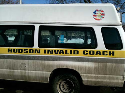 Dirty van with large black letters on the side reading Hudson Invalid Coach