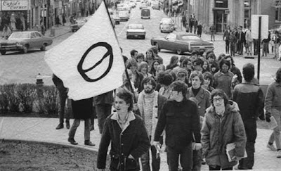 Black and white photo of a small group of young people marching up some stairs, carrying a white flag with the black ecology symbol on it