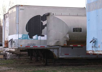 Crouching silhouette on the side of a semi trailer, shot so it looks like he's doing something to the adjacent trailer