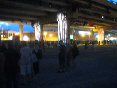 5 story-tall highway overpass at night, shot from below, with crowds of people under it
