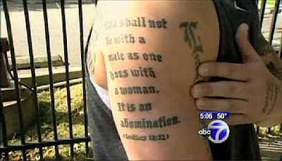 Man showing his right arm, tattoed in blackletter Thou shalt not lie with a male as one does with a woman. It is an abomination. Leviticus 18.22