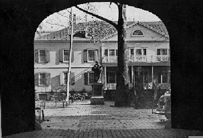 Black and white photo through a darkened archway, courtyard with statue and colonial-style building in background