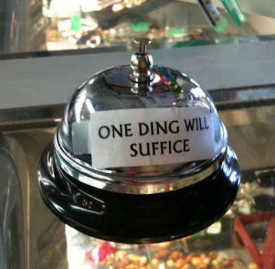 Metal service bell on a counter with a small sign taped on reading ONE DING WILL SUFFICE