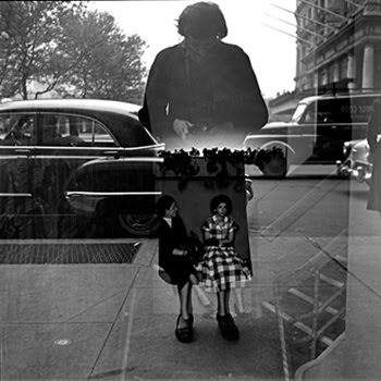 Reflected window photo where Maier is seen in the glass with her camera, two a man and woman, seated, appear to be inside the lower part of her coat