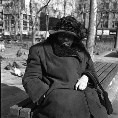 Photo of elderly black woman with beautiful hat hunched on a park bench