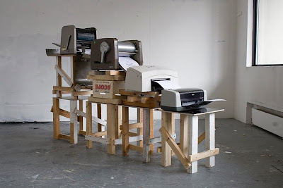 Four printers sitting on different-height tables