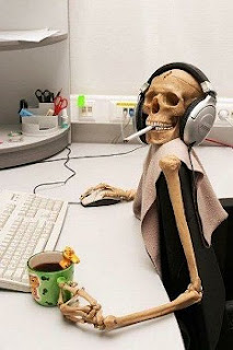 photo of a skeleton sitting at a computer smoking and drinking coffee