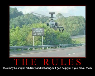 photo of an apache? helicopter hovering behind a speed enforced by aircraft sign