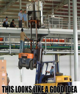 photo of 2 a forklift lifting another forklift