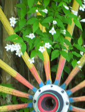 My Handpainted Recycled Wagon Wheel Rolls on Through Spring and Flower Blossoms