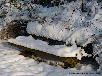 verschneite Parkbank im Stadtpark von Hamburg