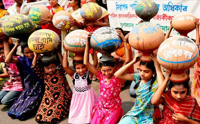 Bangladeshi children carry empty water pots as they perform during a road side dance drama in Dhaka, Bangladesh.