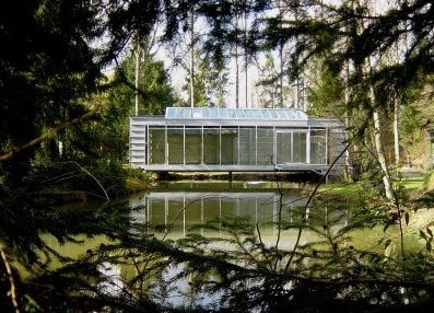 Casa contemporánea como un puente sobre brazo de un lago