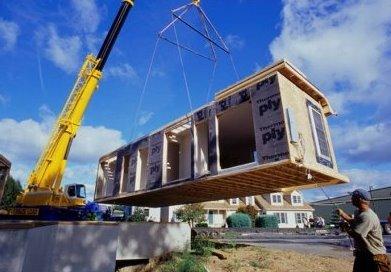 Módulo de madera de una casa en construcción colgando de una grúa
