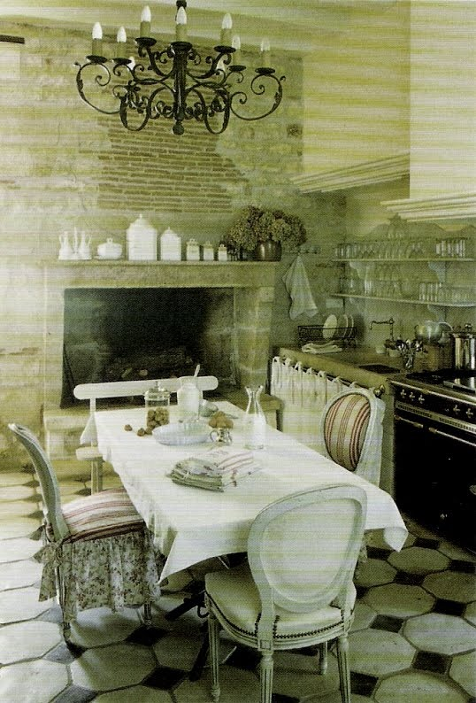 Eat-in kitchen with large stone fireplace, black oven and stove, stone sink, dining table with mismatched chairs, white ceramics, and open shelves, Maisons Cote Ouest, edited by lb for (l&l)