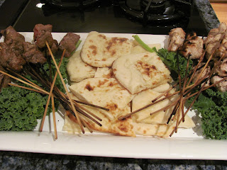 Chicken and lamb skewers and quarted pita on a white tray