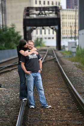Andrea kissing Chris on railroad tracks in Milwaukee for engagement portrait