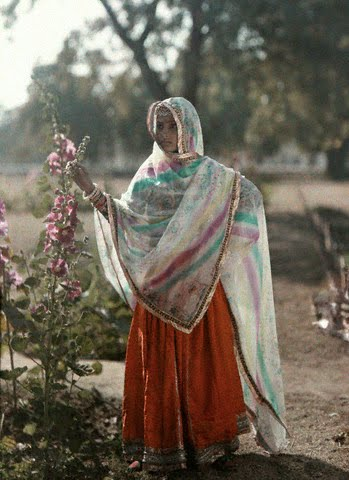 A girl of Agra stands next to a flower bush in traditional clothing - 1926