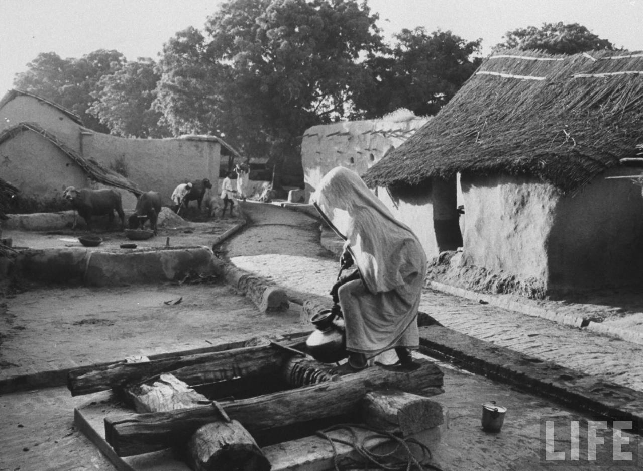 Indian woman drawing water from one of several shallow wells in village - October 1962