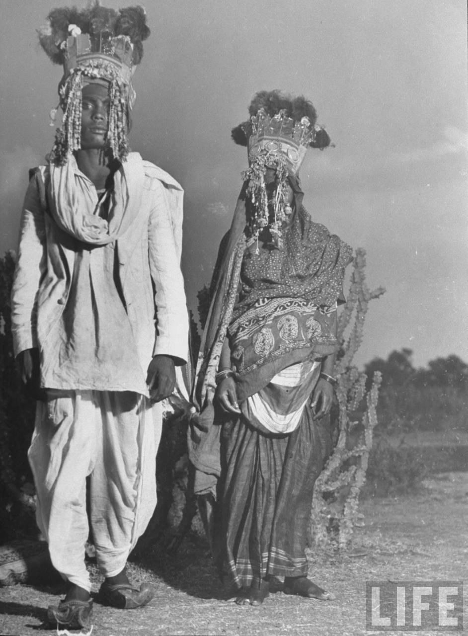 Indian bride & groom wearing ornate headdresses, posing together on their wedding day - 1946
