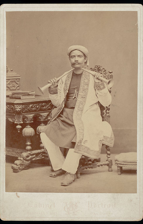 Bengali Man in Costume Holding Two Horns to Throat