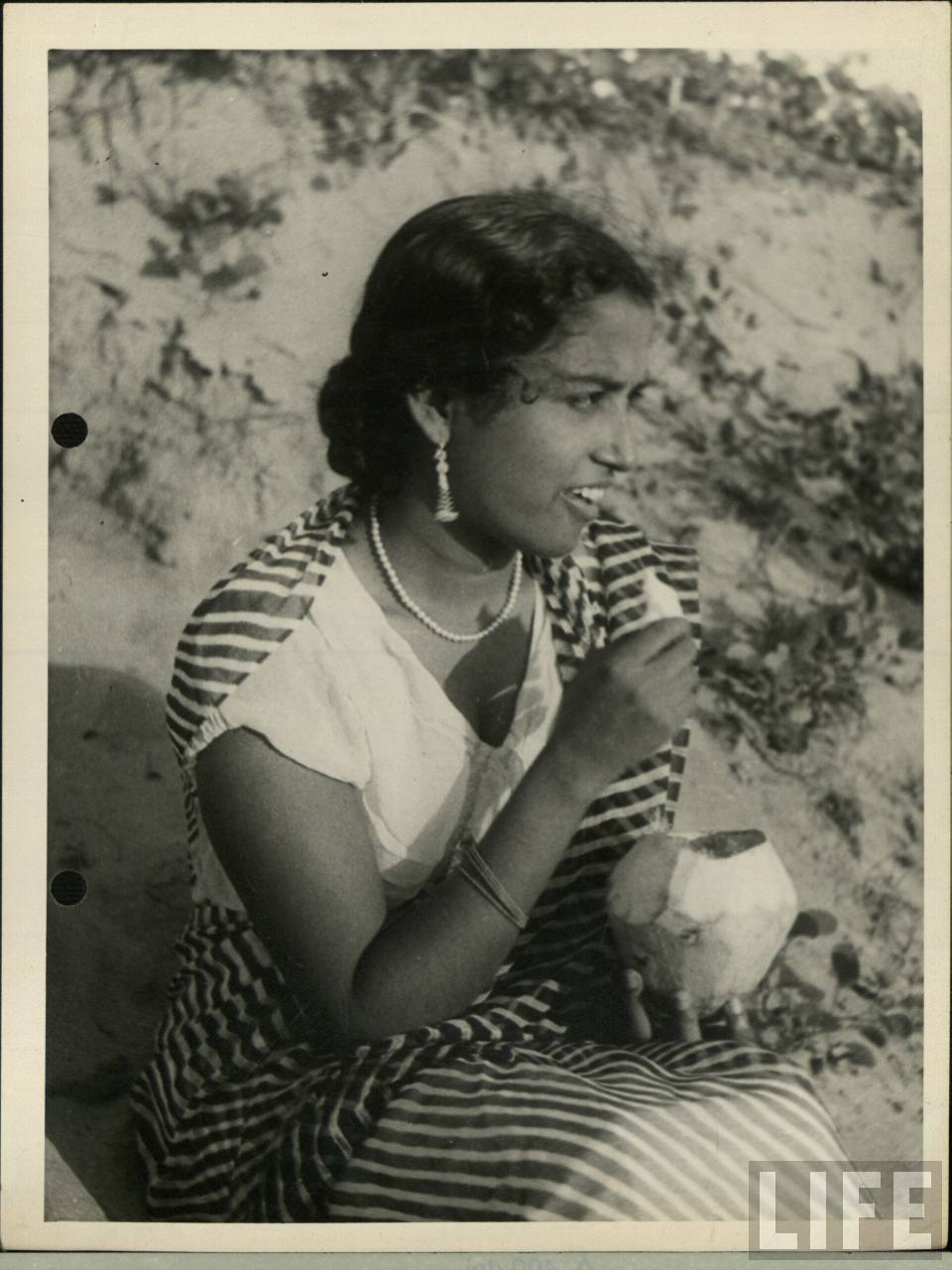 An Indian Woman is Enjoying a Coconut