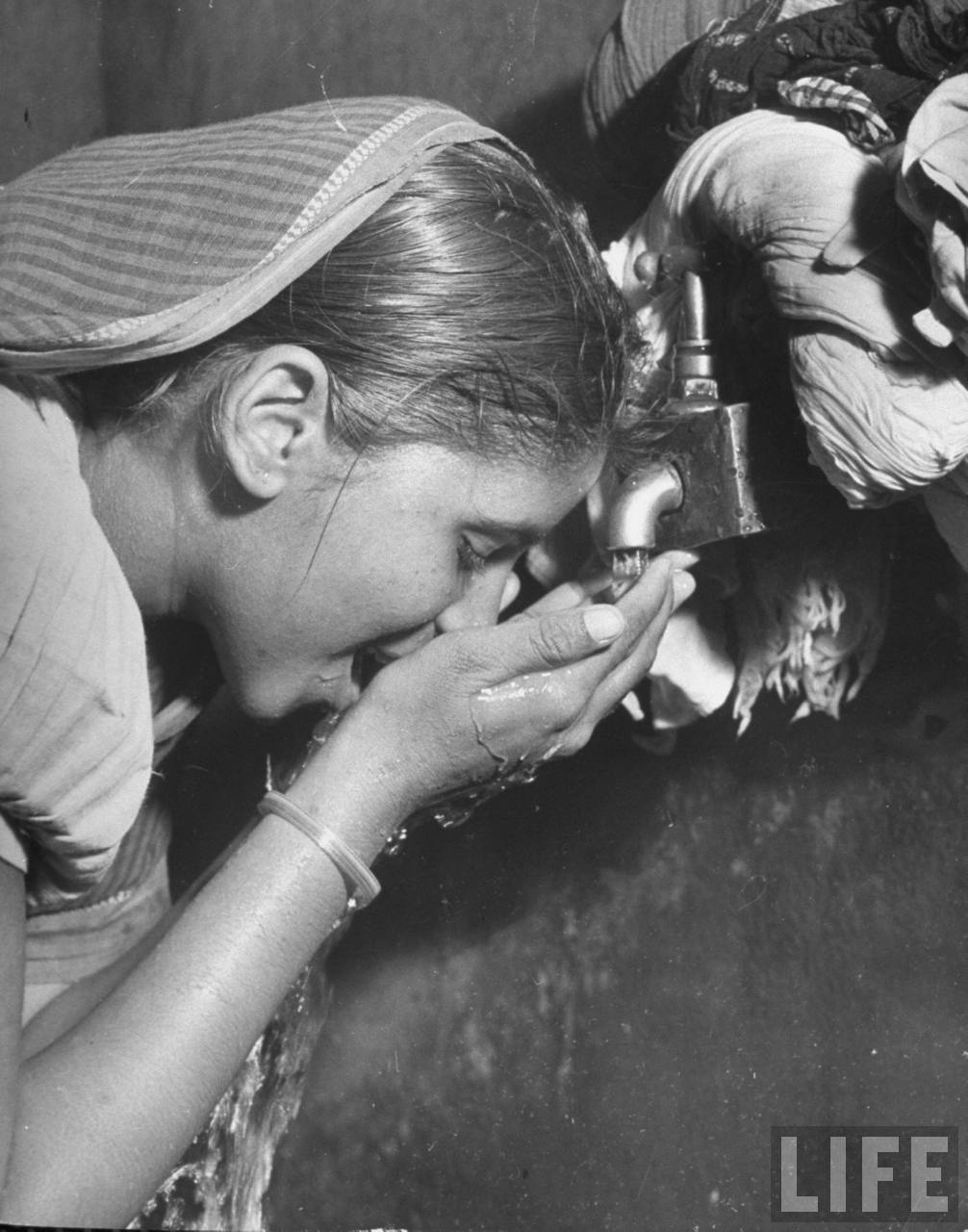 Closeup of a Indian Woman Drinking from Tap at thePublic Water Stand in the Chawls (quarters for the Untouchables) in the Poor Section of theCity - Bombay (Mumbai) 1946