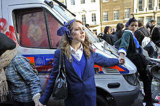 Girls in blue school uniforms holding hands to form a protective circle around the van. The girl in the centre of the shot has a tear drop drawn on her cheek with the caption 'cuts hurt'.