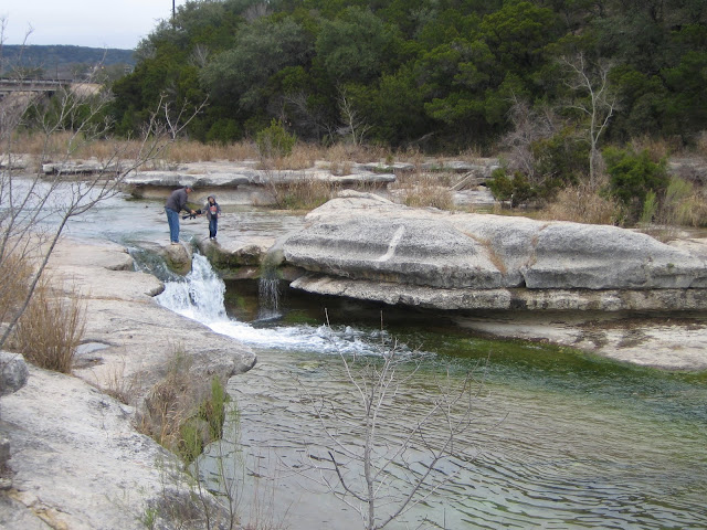 fast flowing creek with people standing next to it