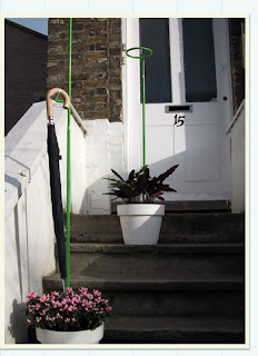 umbrella stand hangs umbrellas over potted plants